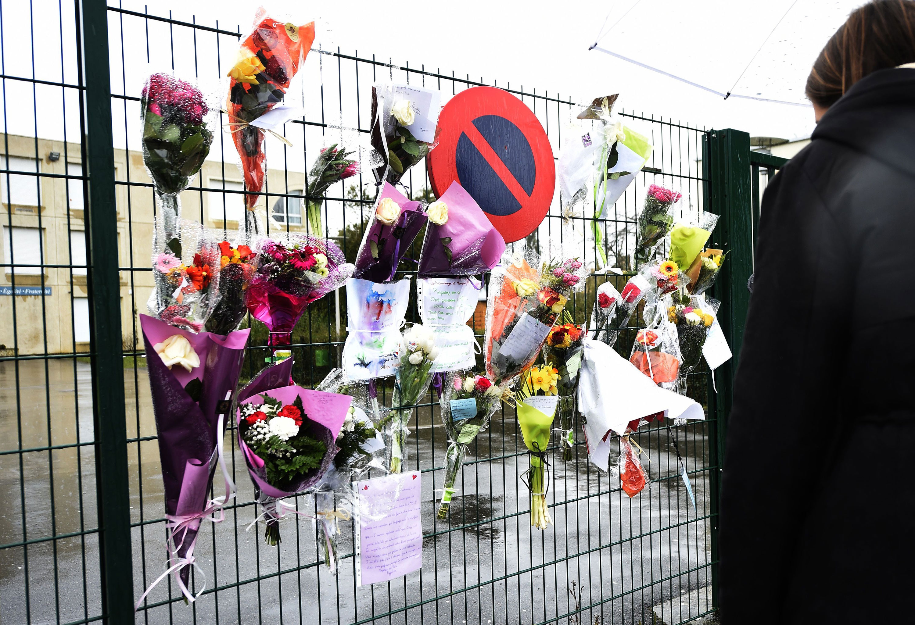 Flowers and letters are placed at the entrance of La Fontaine College in Crepy-en-Valois, France, on Sunday to honor a teacher who died as a result of coronavirus.
